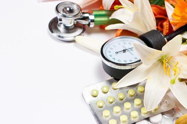 Comprimés, sphingomanomètre et phonendoscope avec fleurs sur blanc.