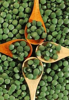 Comprimés de spiruline dans des cuillères en bois, vue de dessus