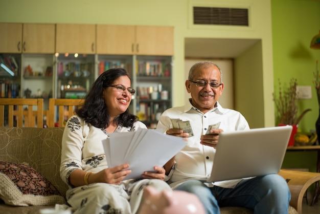 Comptabilité d'un couple asiatique indien senior, faisant des finances domestiques et vérifiant les factures avec un ordinateur portable, une calculatrice et de l'argent également avec une tirelire tout en étant assis sur un canapé ou une table à la maison