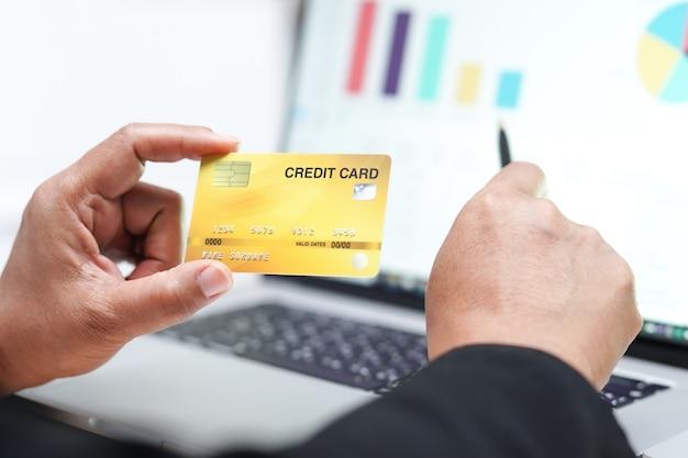 Comptable asiatique détenant une carte de crédit avec graphique.