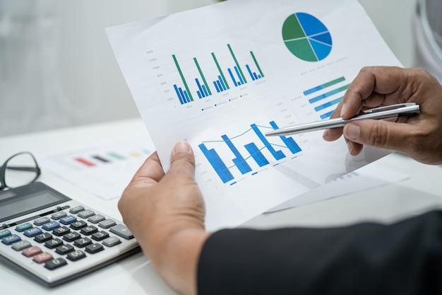 Comptable asiatique travaillant et analysant la comptabilité du projet de rapports financiers avec graphique