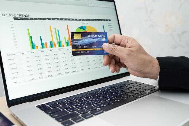 Comptable asiatique travaillant, calculant et analysant la comptabilité du projet de rapport avec ordinateur portable et carte de crédit dans un concept moderne de bureau, de finance et d'entreprise.