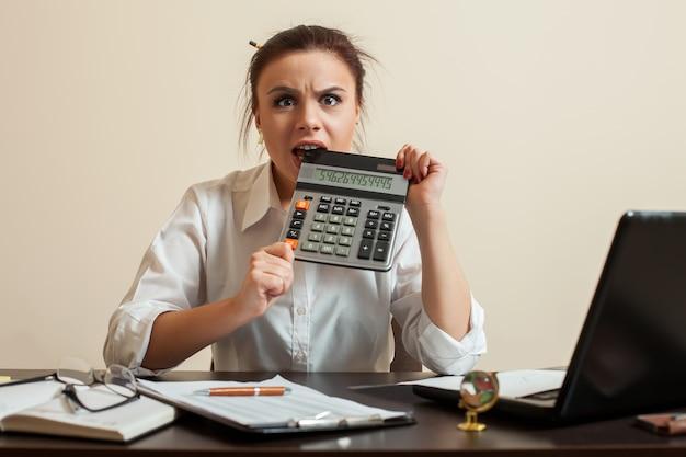 La comptable féminine effrayée ronge la calculatrice