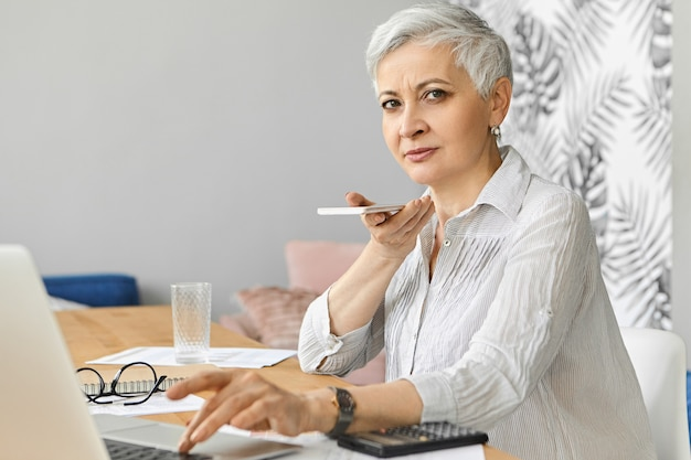 Comptable femme caucasienne aux cheveux gris attrayant occupé à la retraite travaillant comme pigiste gérant les finances, assis au bureau avec un ordinateur portable, tenant un téléphone mobile, enregistrement d'un message vocal