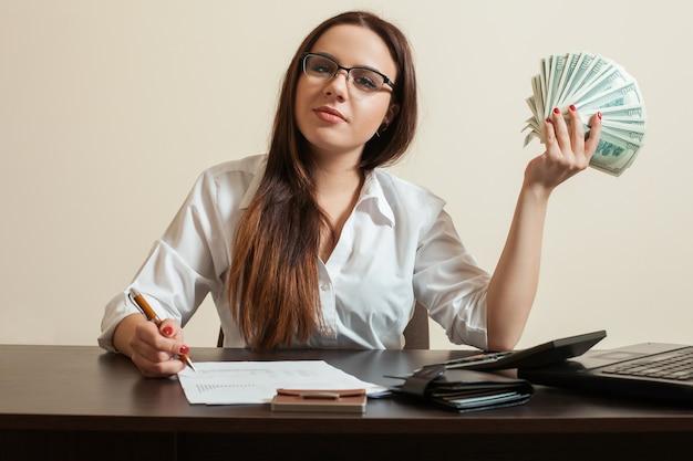 Comptable femme tenant un ventilateur de dollars dans sa main