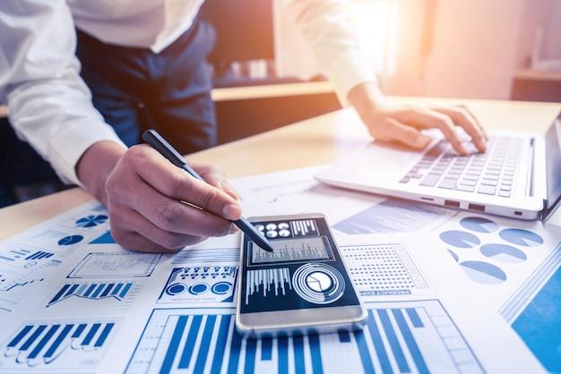 Comptable d'homme d'affaires ou expert financier analysent le graphique du rapport d'activité et le tableau des finances au siège social