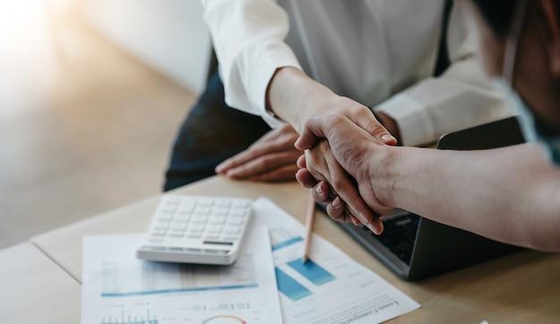 Les comptables financiers et les spécialistes du marketing se serrant la main pour féliciter les performances immobilières, l'étiquette commerciale, les félicitations, le concept de fusion et d'acquisition.