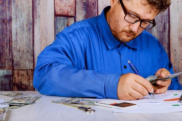 Compte l'argent et écrit le résultat sur la note. billets d'un dollar sur la table comptant des billets en dollars.