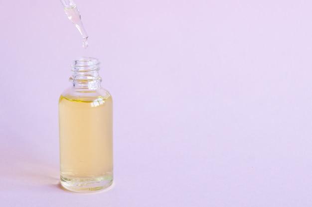 Compte-gouttes bouteille en verre maquette. pipette osmétique sur rose.