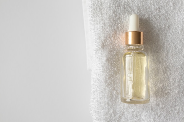 Compte-gouttes d'essence de sérum d'huile sur des serviettes sur fond blanc avec espace de copie.