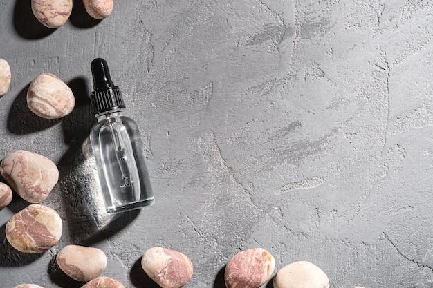 Compte-gouttes d'huile d'essence de soins de la peau dans une bouteille en verre près de cailloux