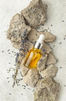 Compte-gouttes d'huile et lavande sur les rochers