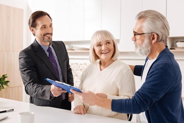 Compte tenu du plan de l'affaire. avocat optimiste intelligent et confiant, rencontre avec un vieux couple de clients tout en travaillant et donnant des conseils professionnels sur l'achat d'une maison
