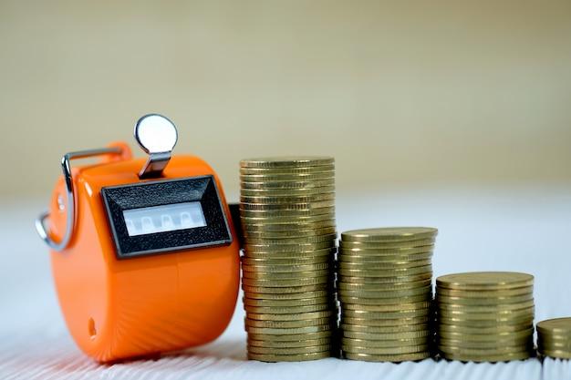 Compteur de billets ou machine à compter avec numéro 0000 et pile de pièces sur bois blanc
