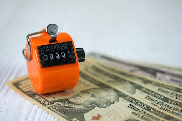 Compteur de caisse ou machine à compter avec numéro 0000 avec pièce et billet de banque sur bois blanc