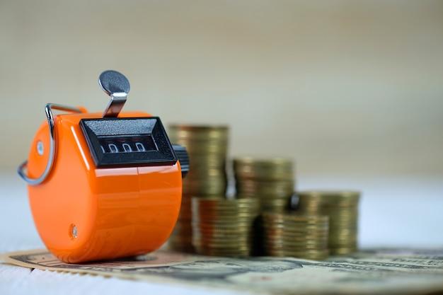 Compteur de comptage ou machine à compter avec numéro 0000, pièce de monnaie et billet de banque sur bois