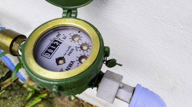 Compteur d'eau sur fond de béton, appareil de mesure, couvercle ouvert du compteur d'eau pour vérifier le nombre de compteurs de consommation d'eau, conduite d'eau et compteur avec trombe marine de la maison