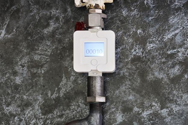 Le compteur de gaz domestique est installé sur un tuyau dans la cuisine sur fond de panneau décoratif