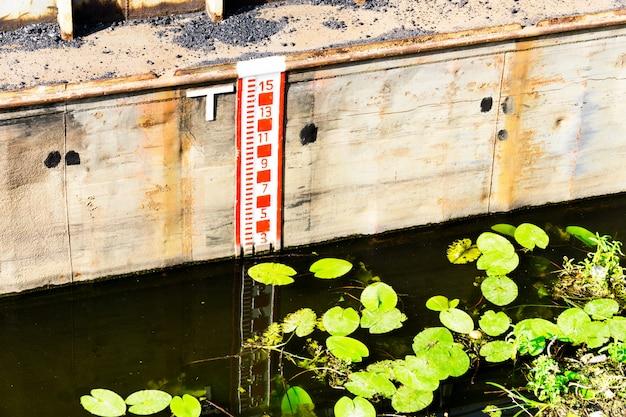 Compteur de niveau d'eau sur un mur métallique.