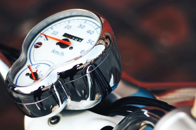 Compteur de vitesse chrome sur une moto. compteur de vitesse blanc avec des flèches rouges.