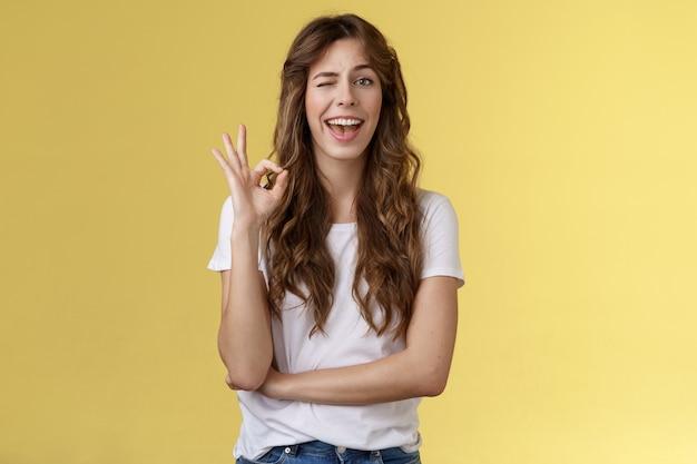 Comptez-moi. une jeune professionnelle effrontée et enthousiaste suggère de ne pas déranger elle a tout sous contrôle montrer d'accord ok geste d'approbation clin d'œil souriant joyeusement hocher la tête jugement positif approbation