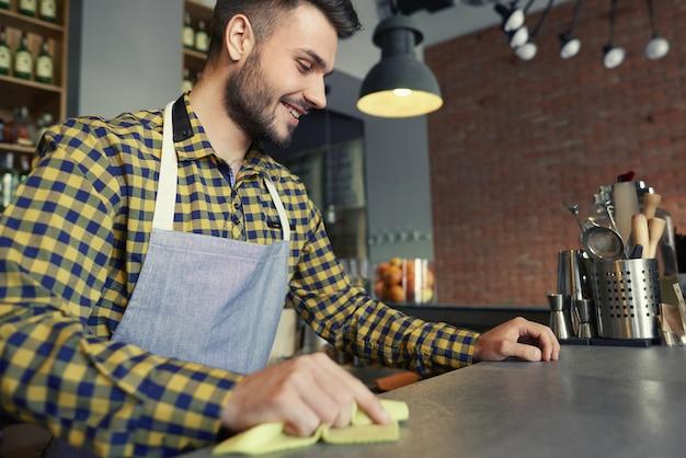 Comptoir de bar de nettoyage de serveur avant le travail