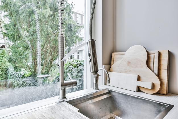 Comptoir de cuisine avec évier en acier inoxydable intégré avec robinet et robinet de filtre dans le coin avec planches à découper empilées