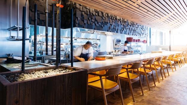 Comptoir de cuisine japonaise avec des chefs faisant omakase, sushi et sashimi au restaurant.