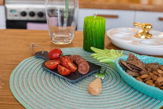 Comptoir de cuisine avec tomates cerises fraîches, saucisses tranchées, amandes, craquelins et belle bougie verte avec plateau d'oeufs en porcelaine avec lapin doré sur le dessus.