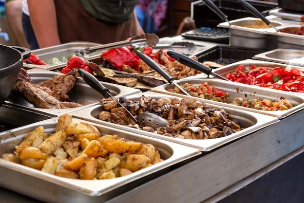 Un comptoir avec des plateaux en métal contenant des aliments grillés. nourriture et matériel de cuisine lors d'un festival de cuisine de rue