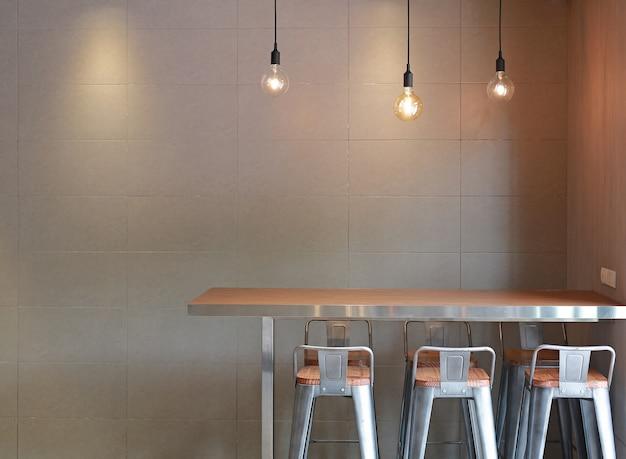 Comptoir de table moderne avec un intérieur en mezzanine avec un mur de carreaux gris et des lampes de décoration suspendues.