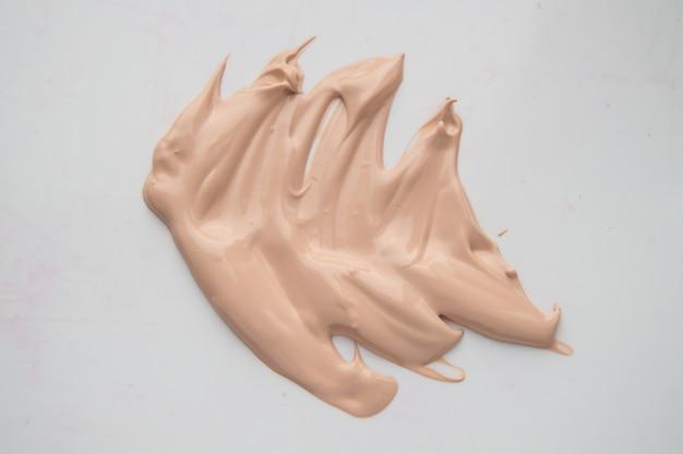 Concealer, maquillage beige clair, base crème smear, fondation sur fond blanc.