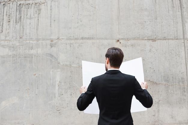 Concentration au travail. vue arrière du jeune homme examinant le plan tout en se tenant à l'extérieur et contre le mur de béton