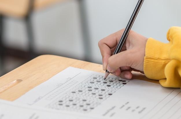 Concentration d'étudiants tenant des crayons dans la main faisant des tests de test de qcm à choix multiples
