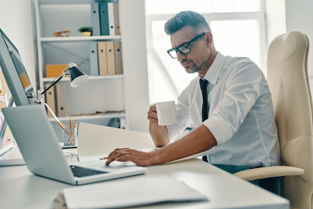 Concentré au travail. beau jeune homme utilisant un ordinateur portable et buvant du café assis au bureau