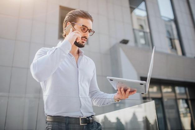 Concentré et beau jeune homme d'affaires se lève et pose. il regarde l'écran de l'ordinateur portable et parle au téléphone en même temps. il y a du bâtiment derrière lui.