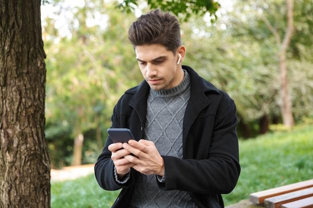 Concentré beau jeune homme en vêtements décontractés marchant à l'extérieur dans un parc verdoyant à l'aide de téléphone portable écoutant de la musique avec des écouteurs.