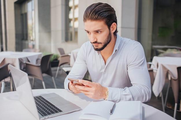 Concentré et calme, le jeune homme est assis attable et regarde l'écran de l'ordinateur portable. il tient le téléphone dans les mains. il y a un cahier ouvert avec un stylo sur la table. il travaille.