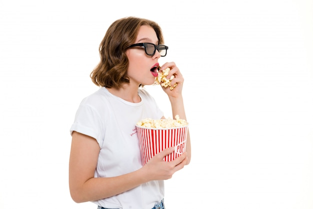 Concentré caucasian woman holding pop corn watch film.