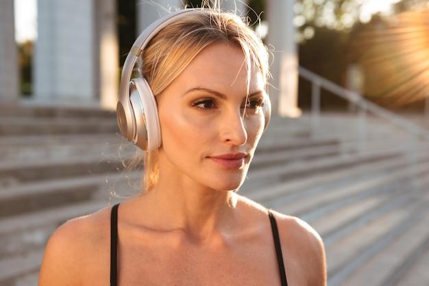 Concentré de forte jeune femme sportive écoutant de la musique