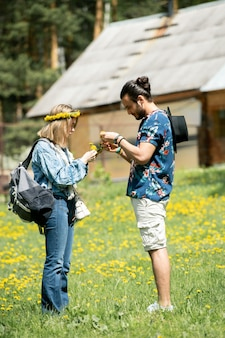 Concentré jeune couple marchant sur le champ de pissenlit et faire une couronne ensemble