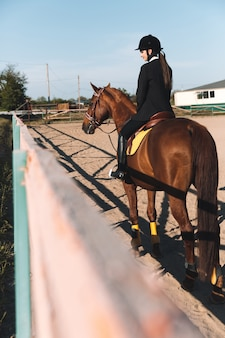 Concentré de jeune femme assise sur son cheval.