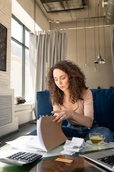 Concentré jeune femme aux cheveux bouclés immergé dans les médias sociaux en tapant sur un ordinateur portable tout en interagissant en ligne dans un café