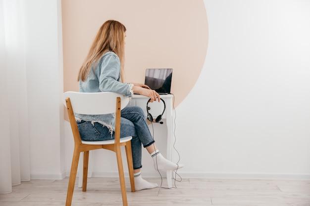 Concentré de jeune femme indépendante assis sur la table à la maison avec un ordinateur portable et des écouteurs