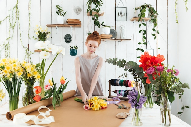 Concentré de jeune femme ramassant un bouquet coloré en atelier