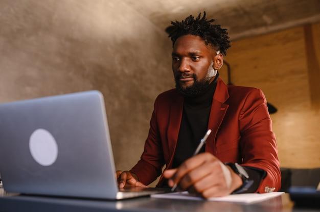 Concentré jeune homme d'affaires africain porter des écouteurs étude en ligne regarder podcast webinaire sur ordinateur portable