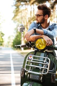 Concentré de jeune homme barbu assis sur un scooter à l'extérieur