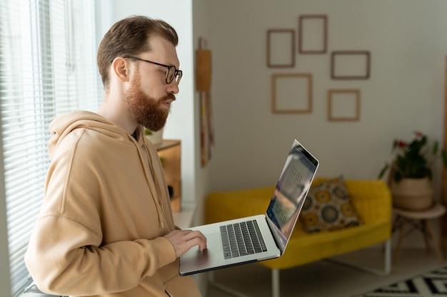 Concentré jeune homme barbu à lunettes debout à la fenêtre et l'analyse de croquis d'interface sur ordinateur portable