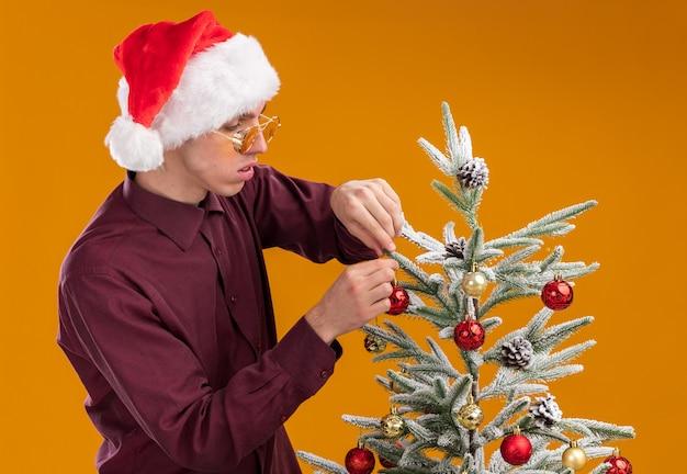 Concentré jeune homme blond portant bonnet de noel et lunettes debout en vue de profil près de sapin de noël en le regardant décorer avec des boules de noël isolé sur fond orange