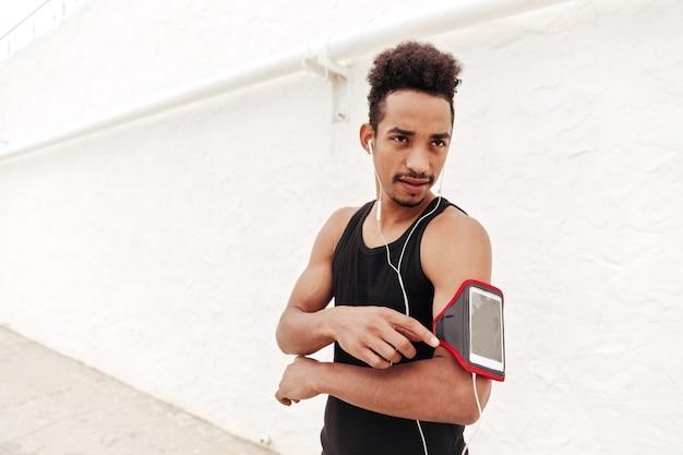 Concentré de jeune homme de sport africain écoute de la musique.